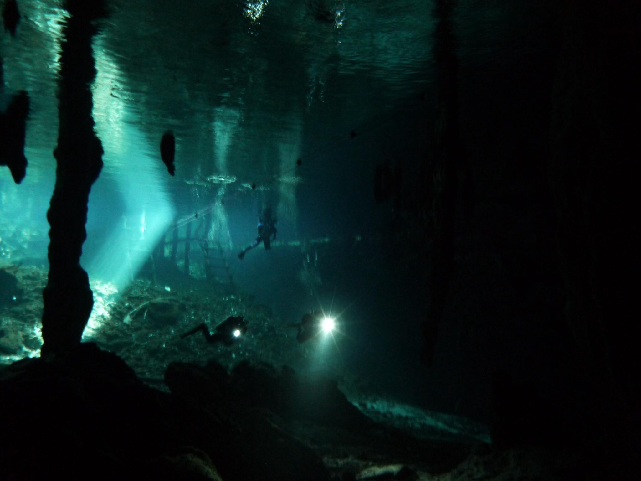 Divers with flashlights at Gran Cenote